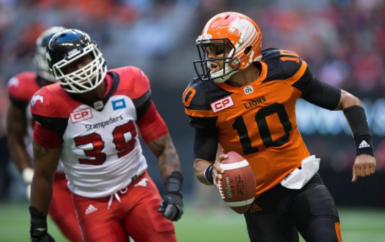 B.C. Lions' quarterback Jonathon Jennings, right, is chased by Calgary Stampeders' Charleston Hughes during the first half of a pre-season CFL football game in Vancouver, B.C., on Friday June 17, 2016. THE CANADIAN PRESS/Darryl Dyck