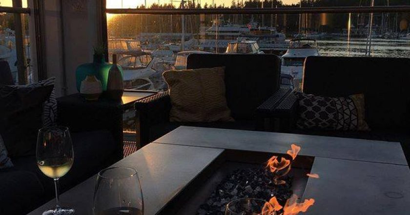 Wine glasses on patio overlooking the water and sunset at Lift in Vancouver