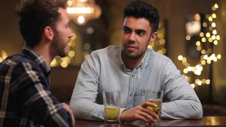 Two men sit at bar with drinks before making a toast together