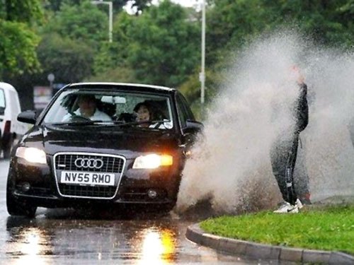 person getting sprayed with water by passing Audi