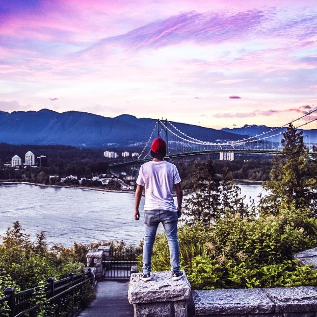 guy standing on ledge looking at lion's gate bridge