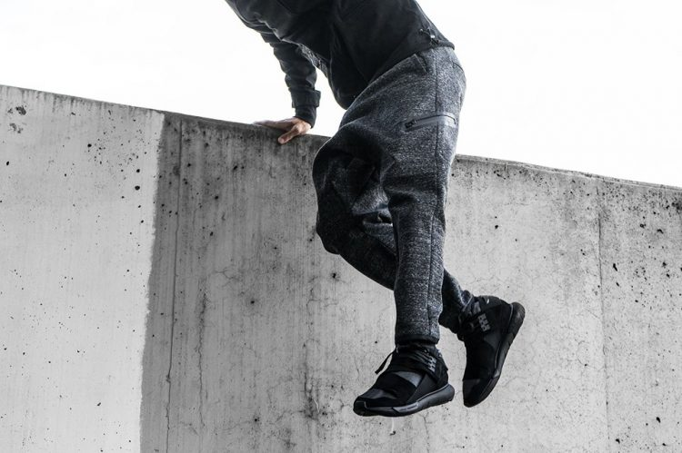 Man jumping over ledge wearing black sneakers
