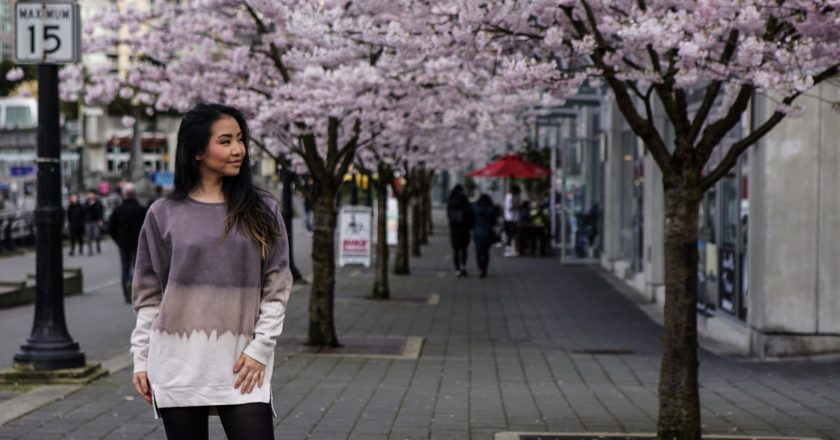 model posing with cherry blossom trees in coal harbour