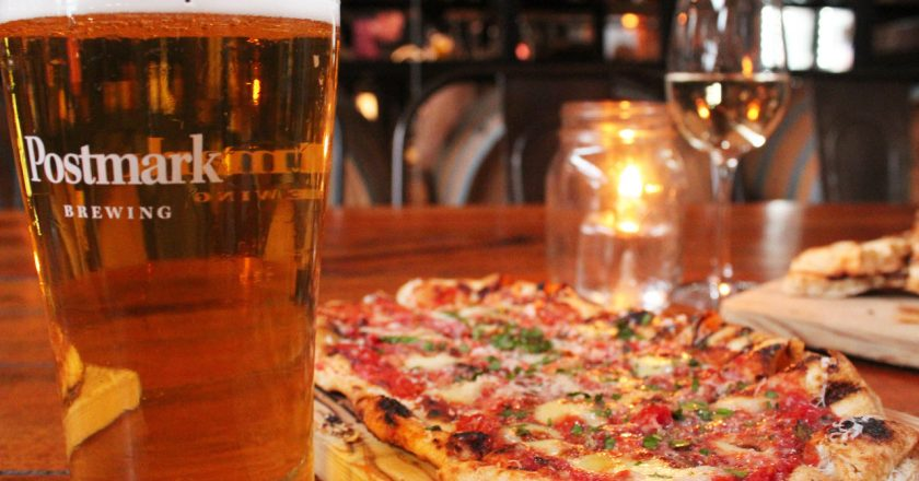 glass of beer and pizza at a restaurant