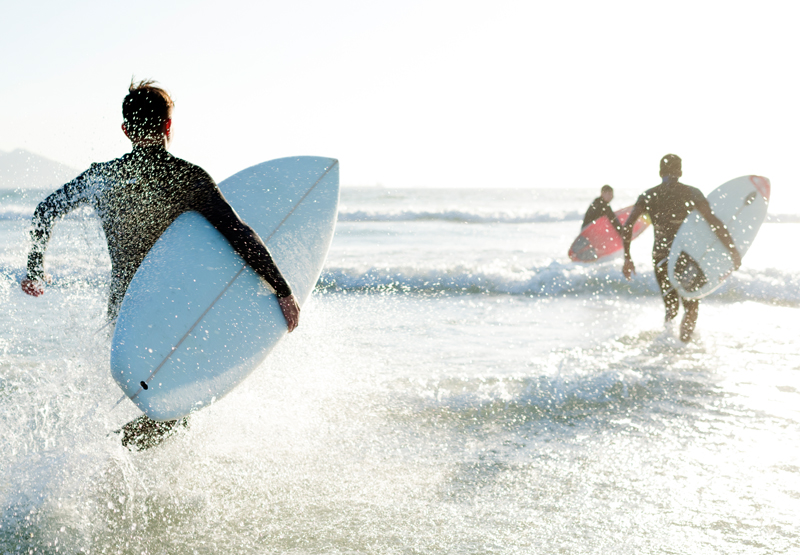 2 people running into the ocean with surfboards