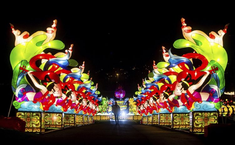 A woman is silhouetted while walking through rows of lanterns during the opening night of the Vancouver Chinese Lantern Festival at the Pacific National Exhibition, in Vancouver, British Columbia, Friday, Dec. 15, 2017. The festival features hundreds of illuminated lanterns and is open until Jan. 21, 2018. (Darryl Dyck/The Canadian Press via AP)