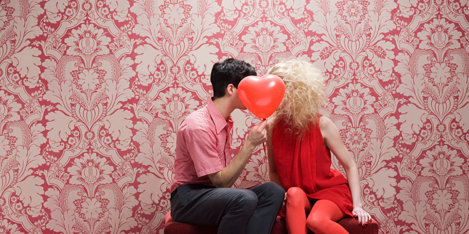 a couple in red kissing behind a heart balloon