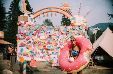 a girl in a donut pool floaty in front a sign of notes